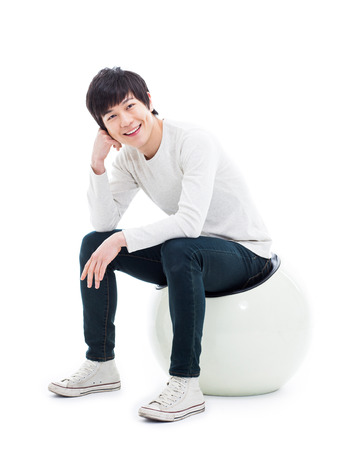 Jonge Aziatische persoon zit op de stoel geïsoleerd op wit. Stockfoto - 25161445