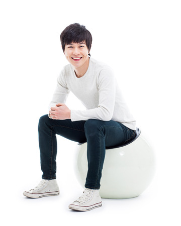 Young Asian person sitting on the chair isolated on white. photo