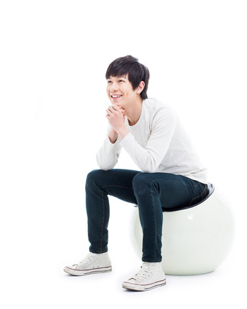 Young Asian man thinking on the chair isolated on white backgroung.  Фото со стока