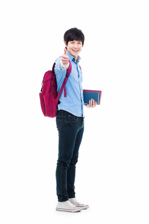 Young Asian student showing thumb isolated on white background. photo
