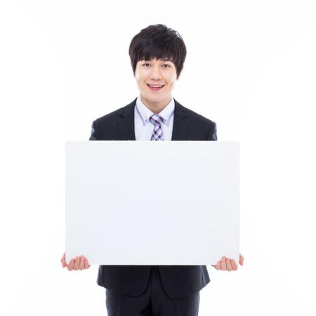 hoja en blanco: Joven hombre de negocios de Asia, con un cartel en blanco aislado en blanco.