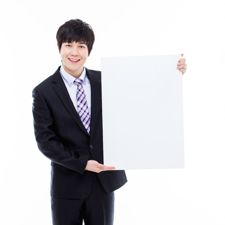 pannel: Young Asian business man holding a blank banner isolated on white background.