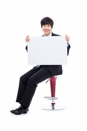 pannel: Young Asian business man holding a pannel isolated on white background.
