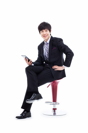 Young Asian business man using a pad PC sitting on the chair isolated on white background.  photo