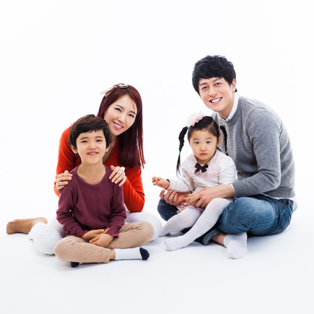 familias jovenes: Familia feliz asi�tica aislada sobre fondo blanco