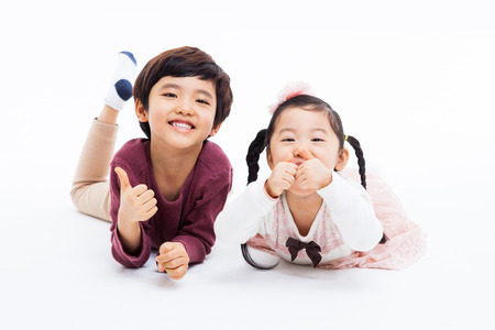 Happy Asian  kids showing thumb isolated on white background