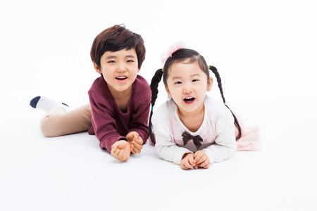幸せな白の背景に分離された横になっているアジアの子供たち