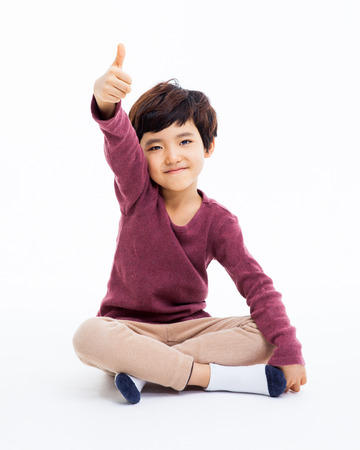 Young Asian boy showing thumb isoalte on white background.