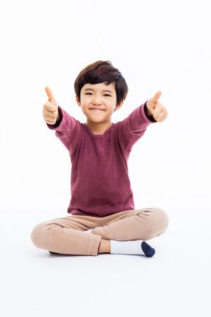 アジアの若い男の子示す親指 isoalte 白い背景の上。