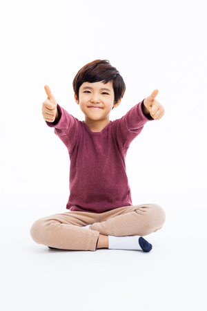 Young Asian boy showing thumb isoalte on white background. Фото со стока - 25793320