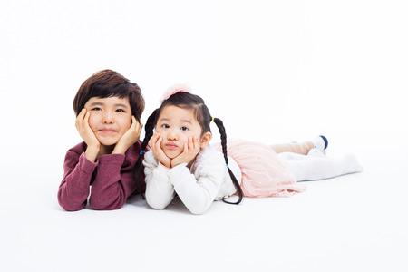 Thinking Asian kids lying isolated on white background.  photo