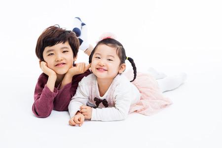 Gelukkige Aziatische kinderen liggen geïsoleerd op een witte achtergrond. Stockfoto - 26198477