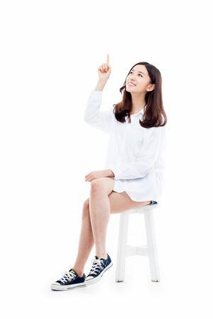 Mujer joven sonriente que señala hacia arriba aislado sobre fondo blanco.