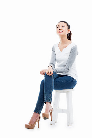 sit studio: Thinking young Asian woman isolated on white background