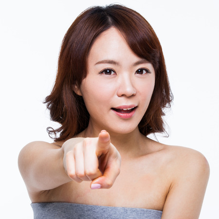 Young Asian woman pointing you isolated on white background. photo