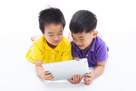 Aziatische jongens met behulp van tablet-pc op wit wordt geïsoleerd. Stockfoto - 35512230