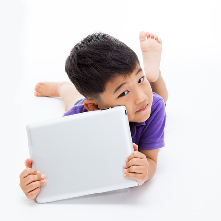 Asian boy using a tablet pc isolated on white. Фото со стока
