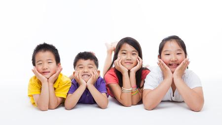 幸せなアジアの子供の分離の白い背景に横たわって。 写真素材