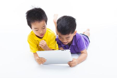 Aziatische jongens met behulp van tablet-pc op wit wordt geïsoleerd. Stockfoto - 35512595
