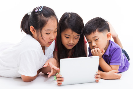 Three Asian kids using a tablet PC isolated on white.