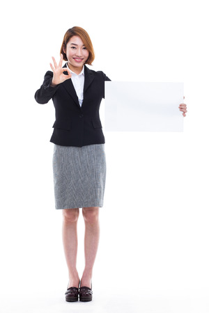 asian businesswoman: Young Asian business woman holding a blank banner isolated on white background.