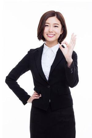 Jonge Aziatische bedrijfsvrouw die ok teken toont dat op witte achtergrond wordt geïsoleerd. Stockfoto