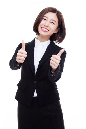 Succesvolle gelukkige Aziatische onderneemster die duim toont die op witte achtergrond wordt geïsoleerd.