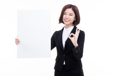 letreros: Mujer de negocios asiática joven que sostiene una bandera en blanco sobre fondo blanco. Foto de archivo