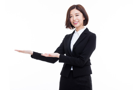 Aziatische zakenvrouw wijzen lege ruimte op een witte achtergrond.