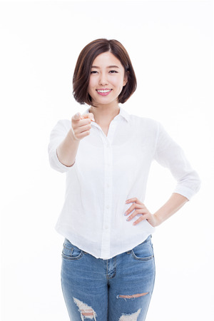 Jonge Aziatische vrouw die u richt op een witte achtergrond. Stockfoto