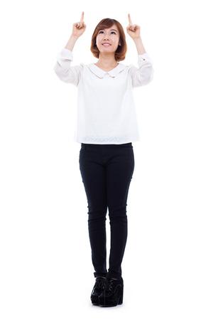 Lachende jonge vrouw wijst naar boven op een witte achtergrond.
