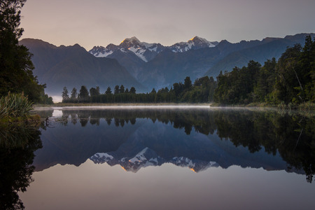 fox glacier: Lake Matheson. Locate near the Fox Glacier in West Coast of South Island of New Zealand.It is famous for its reflected views of AorakiMount Cook and Mount Tasman. Stock Photo