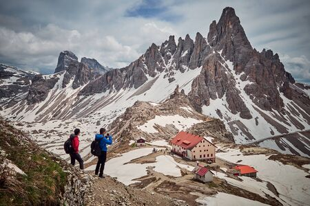Hikers with Tre Cime di Lavaredo in the background, located in Dolomites, Italy