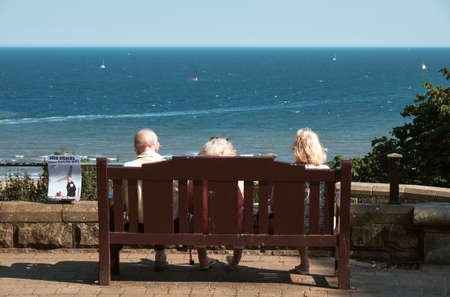 SCABOROUGH, UK - SEP 2, 2018: Old people sitting on a bench near the sea at Scaborough, UK Stock fotó - 149411959