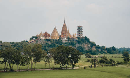 The landscape of Wat Tham Sua from a distance with rice field on a foreground, Thailand 免版税图像