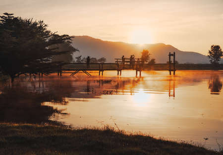 THAILAND, KANCHANABURI - OCT 24, 2019: The landscape of Lam Taphoen reservoir with tourists standing on the bridge near the reservoir at sunrise in Suphan Buri province, Thailand 新闻类图片