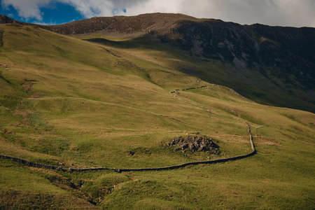 The landscape of countryside road though mountain range in Lake District National Park, Cumbria, United Kingdom