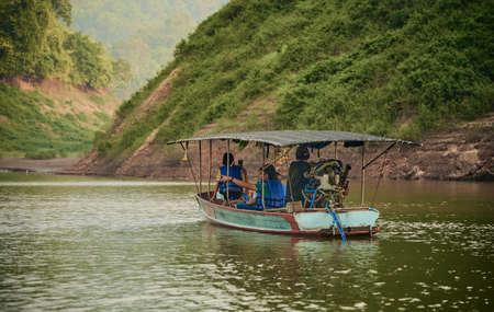 NAKORN NAYOK, THAILAND - MAR 13, 2021: A tourist boat sailing inside Khun Dan Prakan Chon Dam in Nakorn Nayok province, Thailand