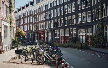 Amsterdam, Netherlands - 4 August, 2019: a lot of bicycle parking in front of colorful building in Amsterdam city with 免版税图像