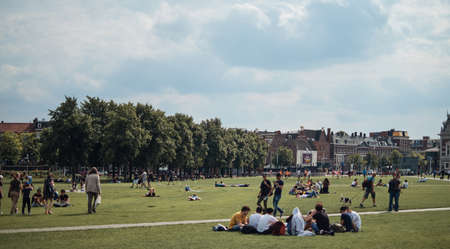 Amsterdam, Netherlands - 4 August, 2019: People walking and relaxing around The Museumplein (Museum square), a public space in the Museumkwartier neighborhood on sunny day 新闻类图片