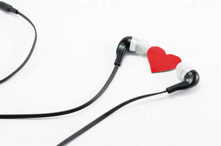red heart and earphones isolated on white background photo
