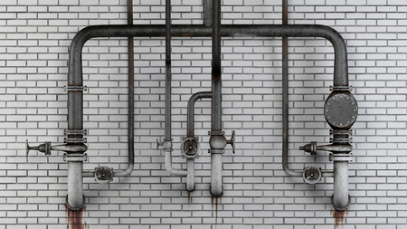 Set of old, rusty pipes and valves against white modern brick wall with leaking stains