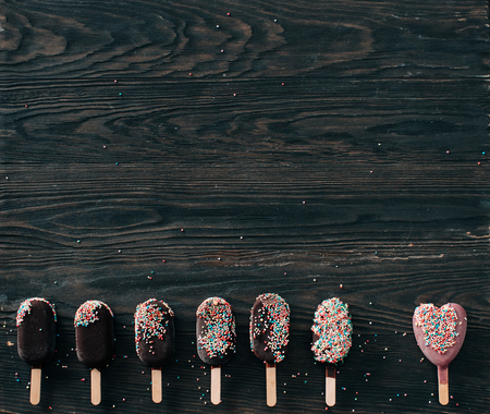 ice cream on a stick lies on a wooden background in different positions