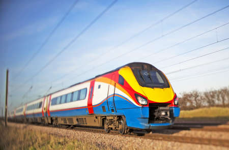 location shot: high speed train thundering by a rural location (shot on TSE glass) Stock Photo
