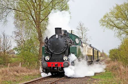 Steam train slowing down to cross a level crossing Stock Photo