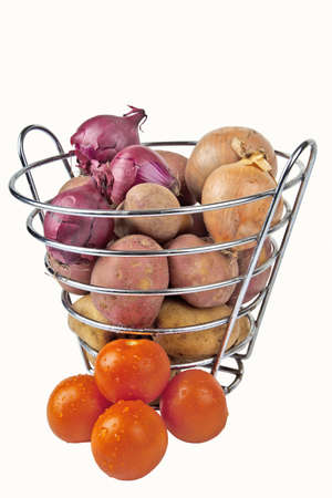 Tomatoes surrounding a basket full of root vegetables - isolated image