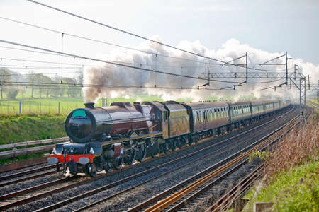mainline: Long haul up - mainline steam train working hard to climb a steep incline with a full load of passengers on board