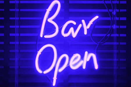 stating: Neon signage stating that the bar is now open to patronage