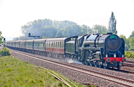 mainline: Steam train on the mainline passing at speed towards the countryside Stock Photo