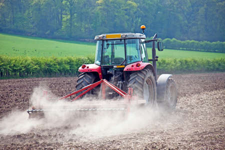 ploughing: Tractor raking over the fields before planting a new seasons crop